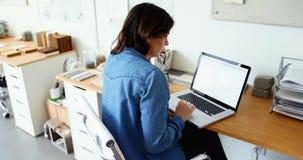 Assento executivo fêmea na mesa e no portátil da utilização filme