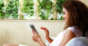 Assento executivo fêmea no sofá e utilização da tabuleta digital vídeos de arquivo