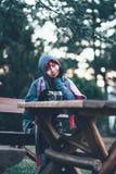 Assento exterior da moça bonita com a câmera na tabela Imagens de Stock