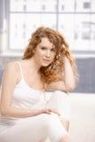 Assento fêmea atrativo no assoalho no estúdio Imagem de Stock