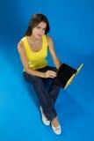 Assento fêmea bonito com um portátil Fotografia de Stock Royalty Free