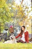 Assento fêmea bonito em uma grama com seu cão em um parque Fotos de Stock