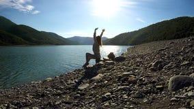 Assento fêmea feliz novo no riverbank nos raios de sol e no esticão, liberdade fotos de stock