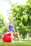 Assento fêmea louro novo em uma bola dos pilates Foto de Stock Royalty Free