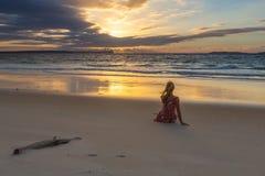 Assento fêmea na areia que olha o nascer do sol fotos de stock