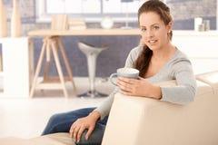 Assento fêmea novo no sorriso bebendo do chá do sofá Foto de Stock