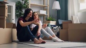 Assento falador dos pares da menina e do indivíduo no assoalho no apartamento novo com caixas da caixa