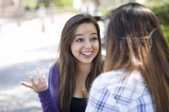 Assento fêmea novo expressivo da raça misturada e fala com menina Fotografia de Stock Royalty Free