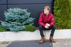 Assento impaciente do menino do adolescente exterior no sentimento do parque furado Fotografia de Stock