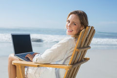 Assento louro lindo na cadeira de plataforma usando o portátil na praia Imagem de Stock Royalty Free