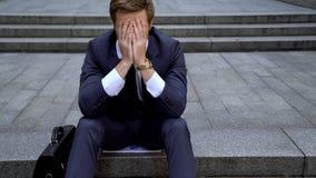 Assento masculino desesperado na escada perto da construção que afrouxa todo o dinheiro no mercado de valores de ação fotografia de stock royalty free