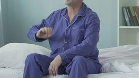 Assento masculino idoso na borda da cama após levantar-se, esticar e sorrir video estoque