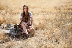 Assento modelo bonito em um coto em um campo no nascer do sol Foto de Stock