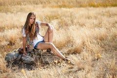 Assento modelo da jovem senhora bonita em um coto em um campo no nascer do sol Foto de Stock Royalty Free
