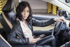 Assento modelo da mulher bonita no carro com telefone à disposição Imagem de Stock