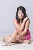 Assento modelo fêmea com um fundo cinzento Fotografia de Stock Royalty Free