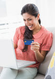 Assento moreno alegre em seu sofá usando o portátil para comprar onlin Fotos de Stock