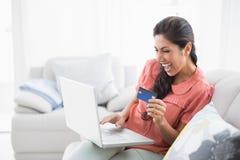 Assento moreno ectático em seu sofá usando o portátil para comprar em linha Fotografia de Stock Royalty Free