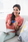Assento moreno entusiasmado em seu sofá usando o portátil para comprar em linha Fotografia de Stock Royalty Free