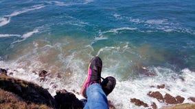 Assento no penhasco da borda Vista superior do penhasco aos pés acima da ressaca imagens de stock royalty free