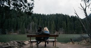 Assento novo dos pares no banco de madeira Olhou o lago Vista no amor um com o outro vídeos de arquivo