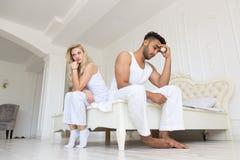 Assento novo dos pares separado na cama, tendo o problema dos relacionamentos do conflito, homem latino-americano das emoções neg fotografia de stock