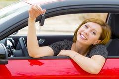 Assento orgulhoso de sorriso da mulher atrativa feliz nova no banco do condutor que realiza e que mostra a chave do carro na comp Fotografia de Stock Royalty Free