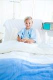 Assento paciente da criança em uma cama de hospital Fotografia de Stock