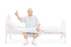 Assento paciente maduro em uma cama e da doação em um polegar acima Fotos de Stock