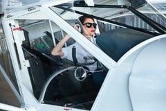 Assento piloto da jovem mulher bonita na cabine de aviões pequenos Fotografia de Stock Royalty Free