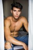 Assento 'sexy' do homem novo descamisado por cortinas Fotos de Stock
