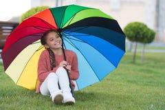 Assento sob o guarda-chuva e ter o divertimento Menina pequena na chuva de espera do parque Guarda-chuva colorido como o conceito foto de stock