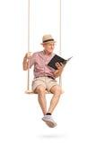 Assento superior alegre no balanço e na leitura um livro imagens de stock