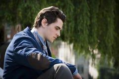 Assento triste, preocupado do homem novo exterior na cidade Imagem de Stock