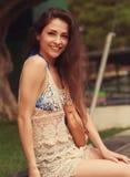 Assento urbano feliz da jovem mulher exterior Imagem de Stock