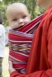 Assento velho de seis meses da menina bonito pequena no estilingue fotos de stock