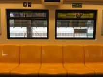 Assentos amarelos no skytrain para na estação de destino imagens de stock