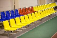 Assentos coloridos em um estádio na sala Fotos de Stock