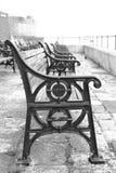 Assentos de banco preto e branco na frente marítima em Portsmouth velho Fotografia de Stock