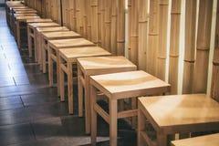 Assentos de madeira da cadeira na parede do bambu da loja do restaurante de Japão da fileira fotos de stock