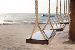 Assentos de madeira de suspensão do balanço em uma barra na praia fotos de stock royalty free