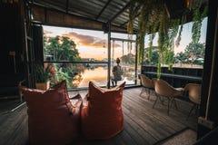Assentos e tabelas do restaurante do beira-rio perto de Chiang Mai durante o por do sol em Lampang, Tailândia foto de stock royalty free
