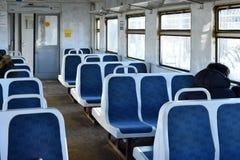 Assentos plásticos azuis velhos em um trem suburbano em Moscou, Rússia foto de stock