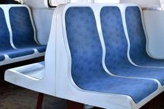 Assentos plásticos azuis velhos em um trem suburbano em Moscou, Rússia fotos de stock