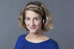 Assertief jong blond wijfje die oortelefoons dragen royalty-vrije stock afbeelding