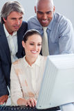 Assertive business people working at a computer Stock Photography