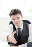 Assertive businessman holding out his hand Stock Images