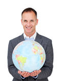 Assertive businessman holding a terreatrial globe. Isolated on a white background stock images
