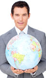 Assertive businessman holding a terrestrial globe Stock Image