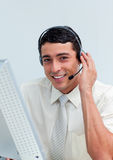 Assertive businessman using headset. Working at a computer Stock Photo